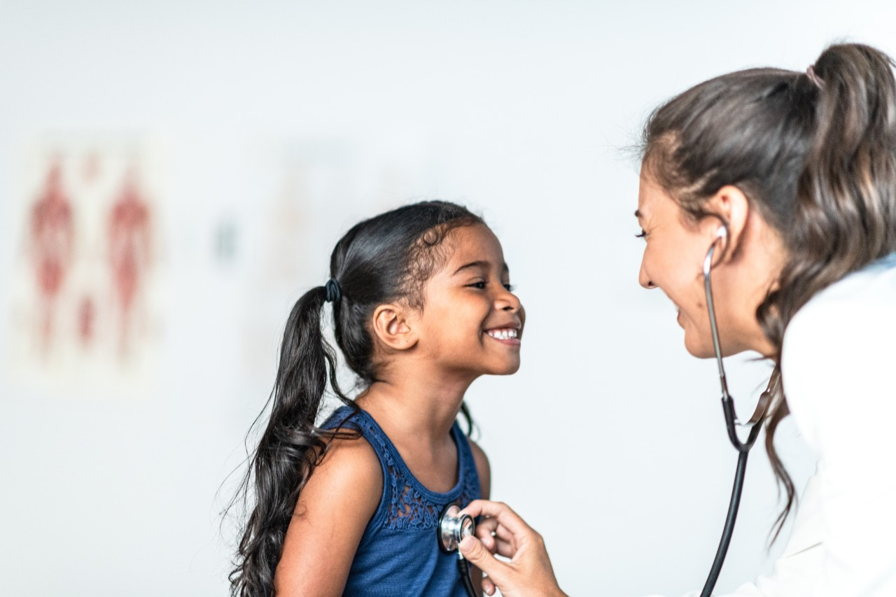A young East Indian girl is examined by her Hispanic female doctor.  The doctor is checking her heart with the stethoscope that is around her neck.  The young girl is wearing a blue tank top while the doctor is wearing a white lab coat.